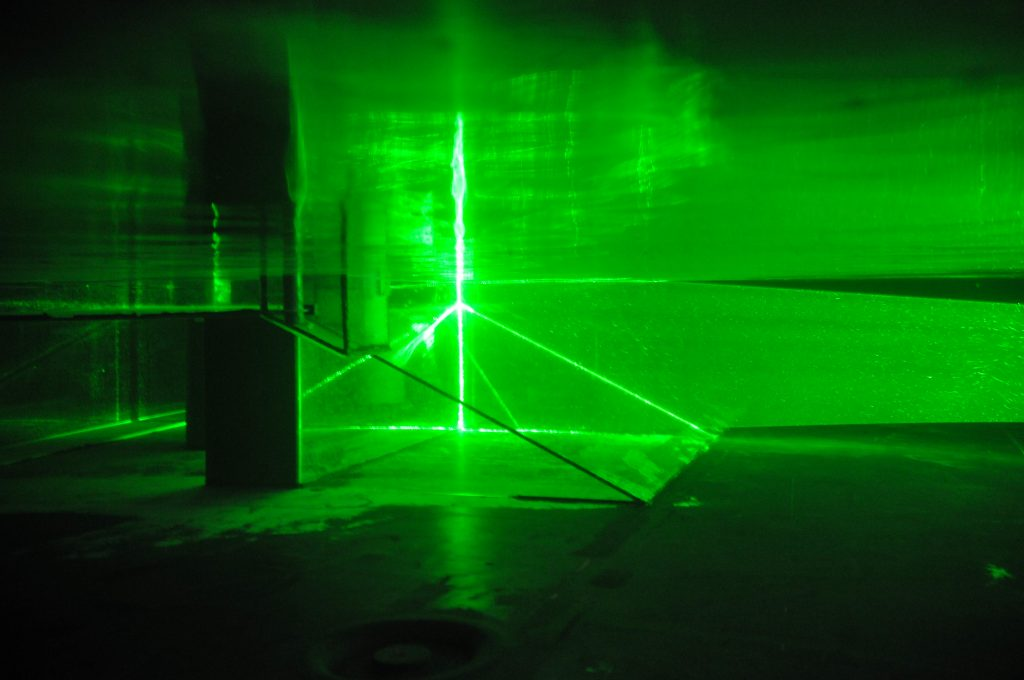 Green laser beams in the water, reflecting off of our topography