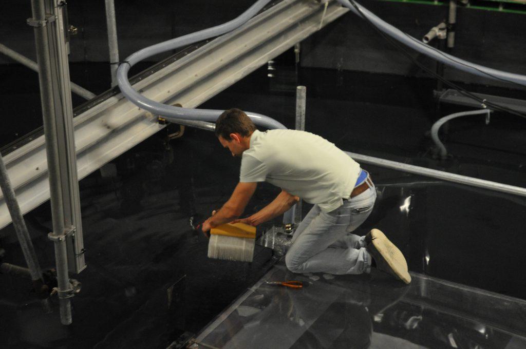 Thomas kneeling on Antarctica, fixing the source