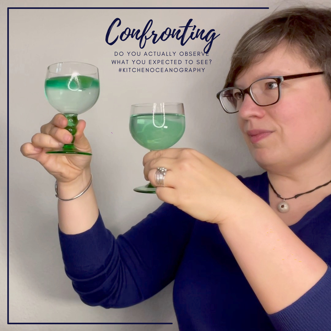 Photo & text: Mirjam @meermini holding up two wine glasses which she looks critically at, both with green ice cubes floating in them. One glass contains clear water with a thin green layer on top, the other glass contains green water